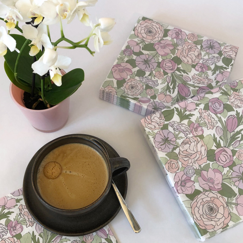 Photo of napkins with flower design surrounded by a cappuccino and little orchid.