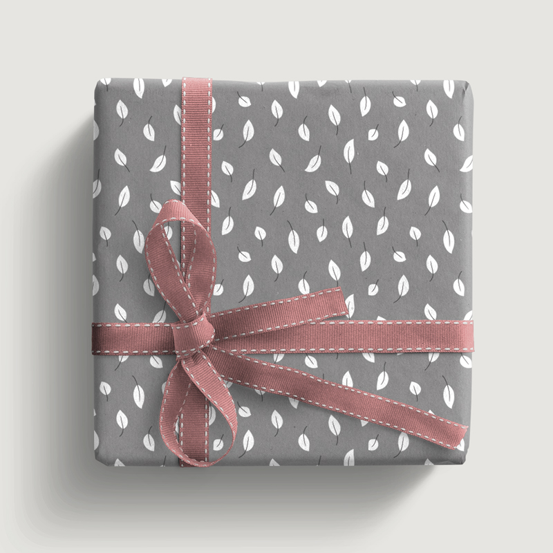 Picture of a gift with graphical wrapping paper in grey with light white leafs and old rose ribbon bow.