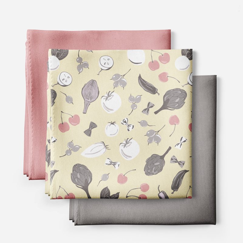 The picture shows fabric swatches of textile design in solid pink and grey and seamless pattern design with healthy food.